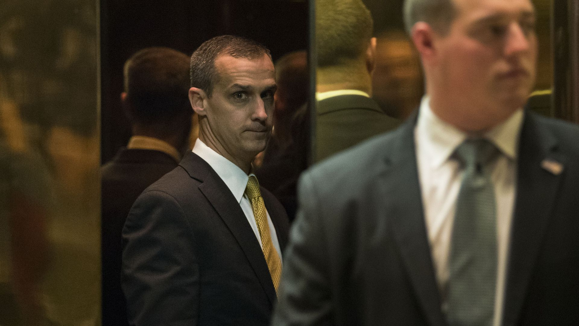 Corey Lewandowski seen between gold elevator doors looks disconcerted.