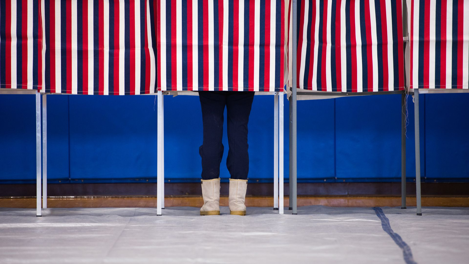 Pair of feet in blue pants underneath polling booth with red, white, blue stripes.