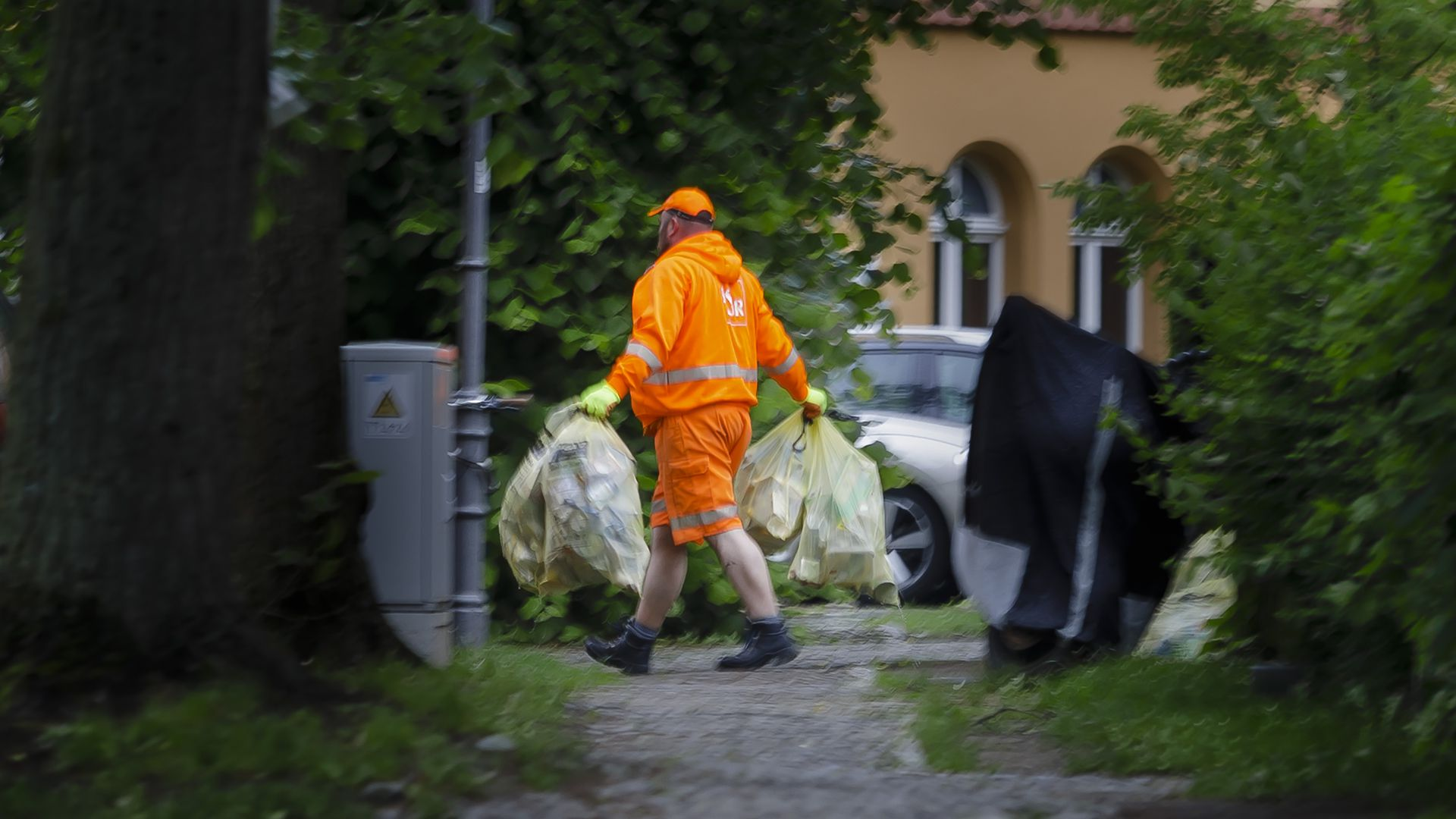 A garbage man carries bags of plastic waste for recycling