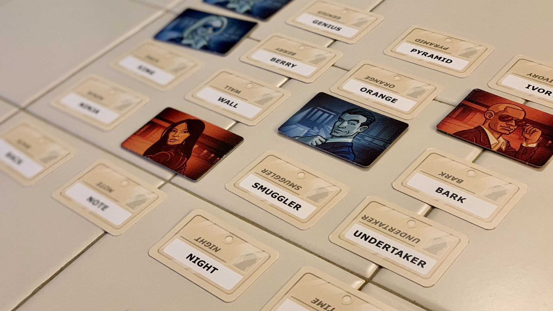 Photo of a game board with a grid of 25 words, some covered by cards