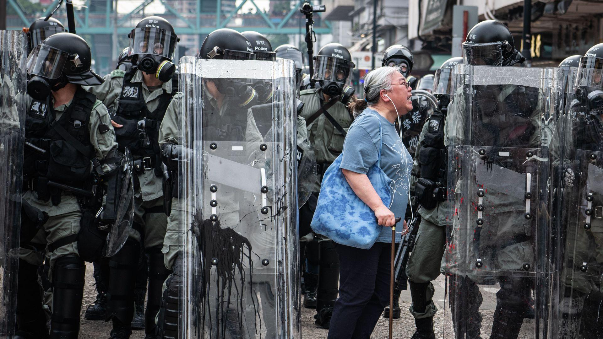 A woman screams at riot police