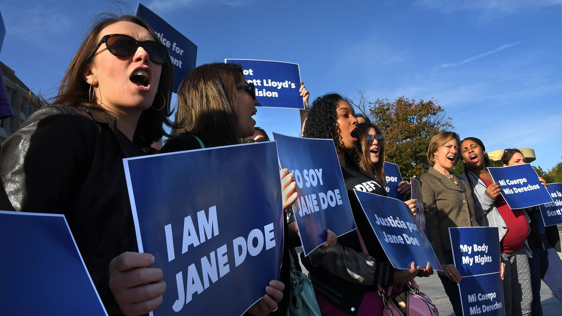 "Women protesting with blue signs that say ""I AM JANE DOE"""
