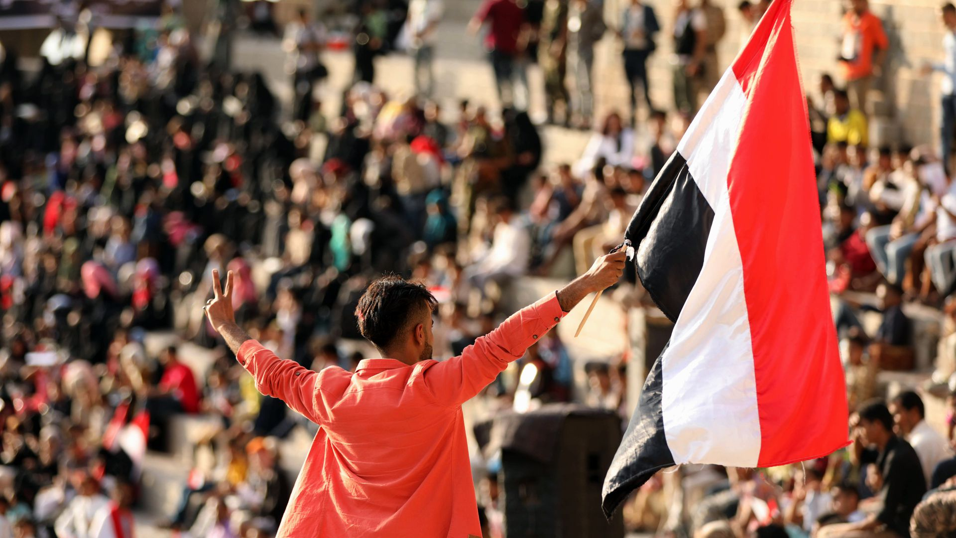 A young person waves a Yemen flag in front of a crowd.