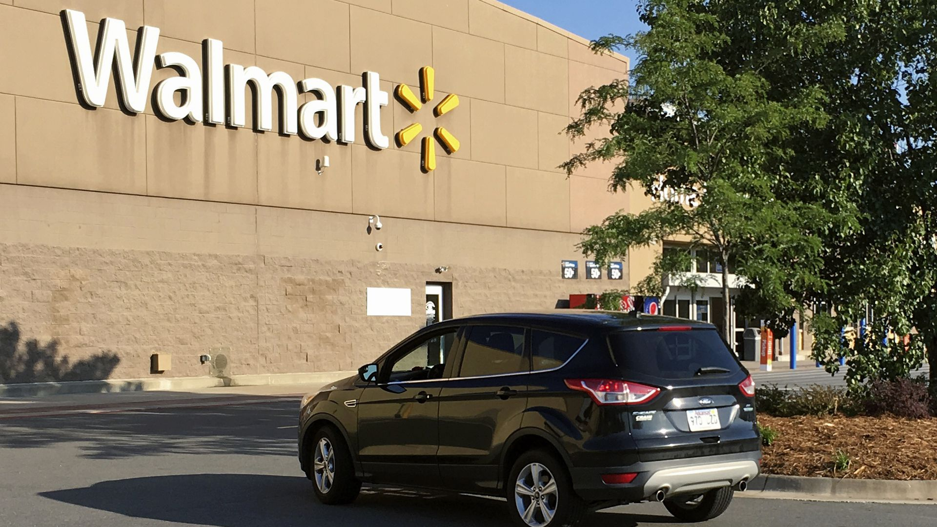 A motorist drives through a Walmart parking lot.