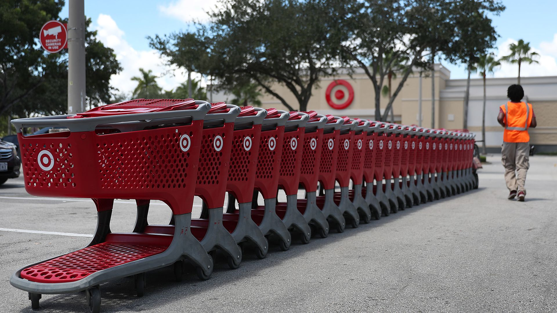 In this image, a Target employee in an orange vest stands next to a line of Target shopping carts.