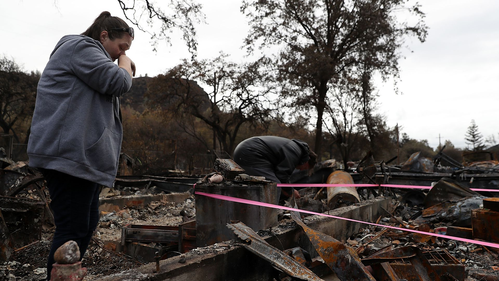 A woman stands in burned ruins of her home.
