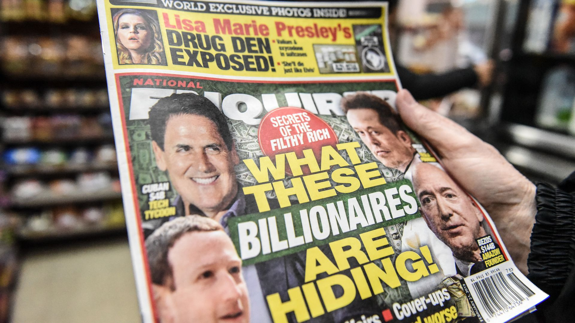 In this image, a copy of the National Enquirer is held up close to the camera by an unseen person.