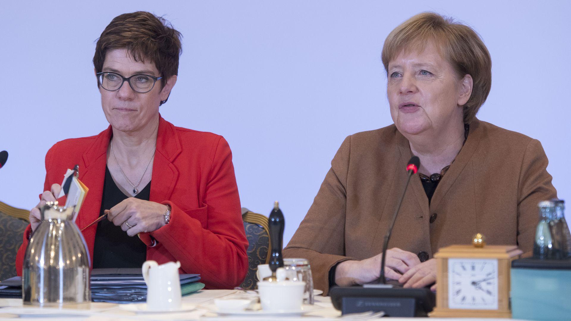 Angela Merkel and AKK seated at a CDU party event