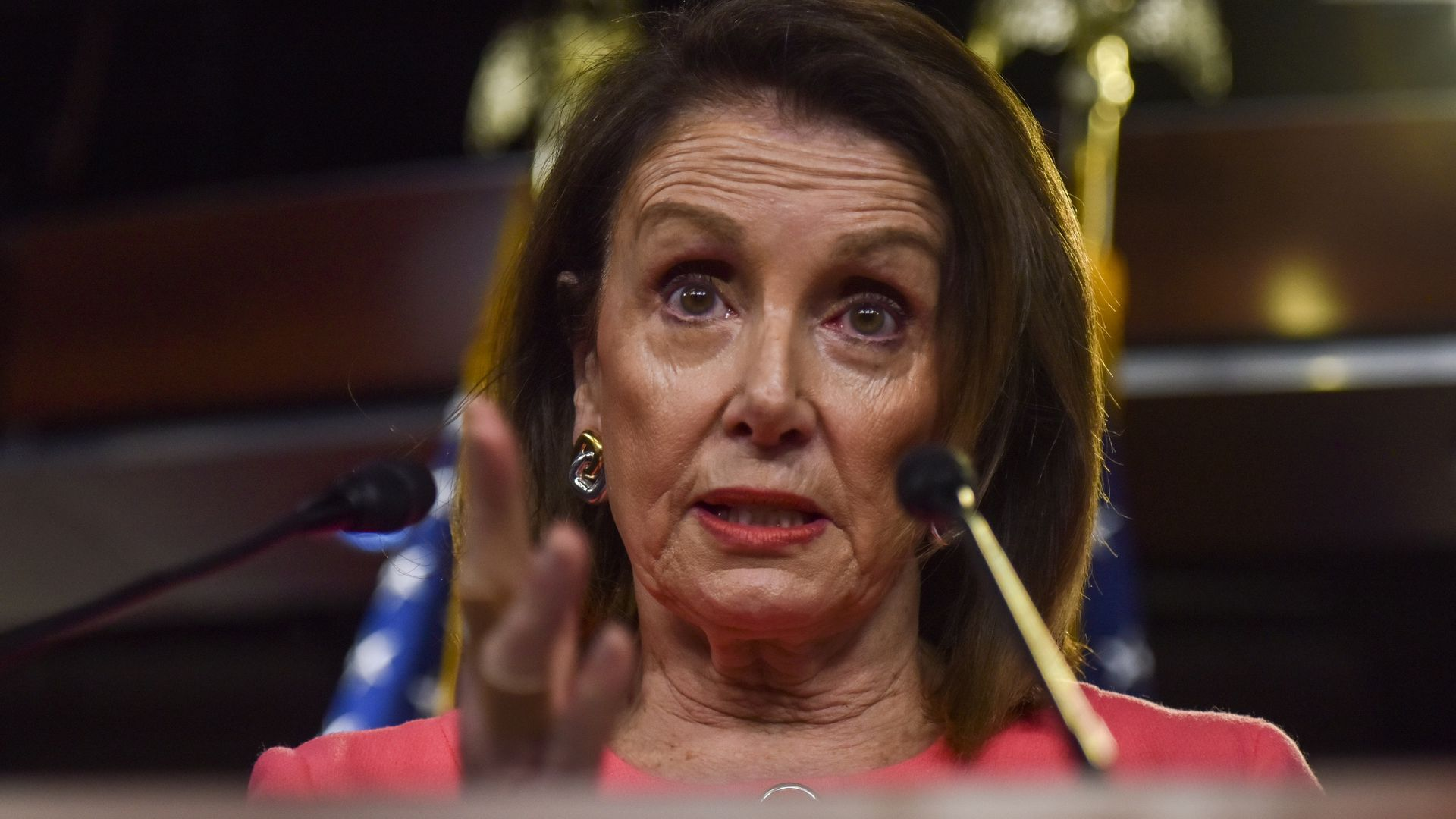 In this image, Pelosi gestures from behind a podium.