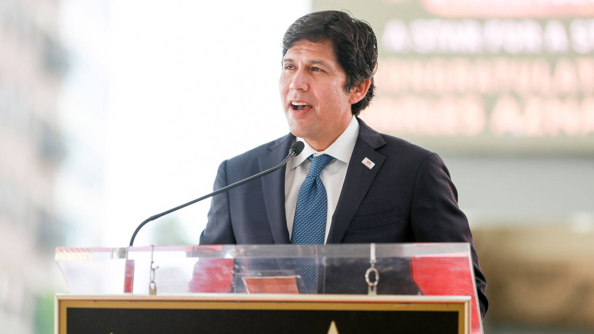 Kevin de León wearing a suit and speaking from a podium