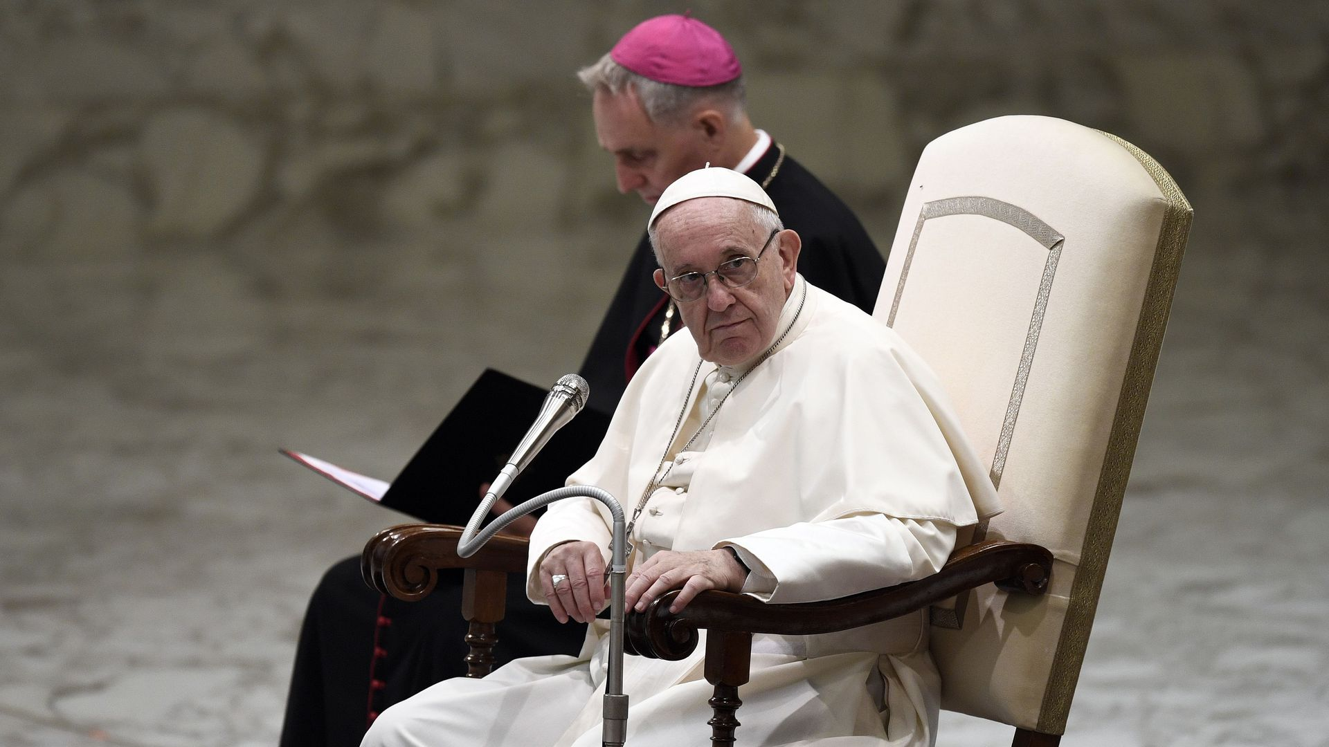 The pope sitting in a chair looking to the side, looking serious.