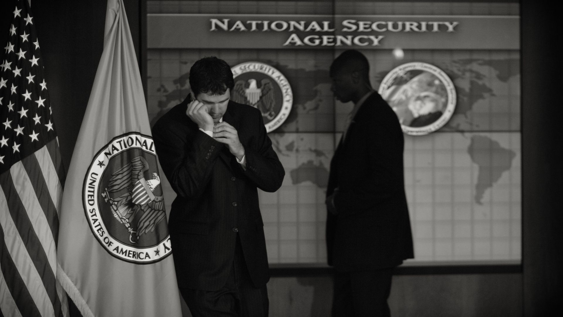 "Two men stand below text that reads ""National Security Agency"""