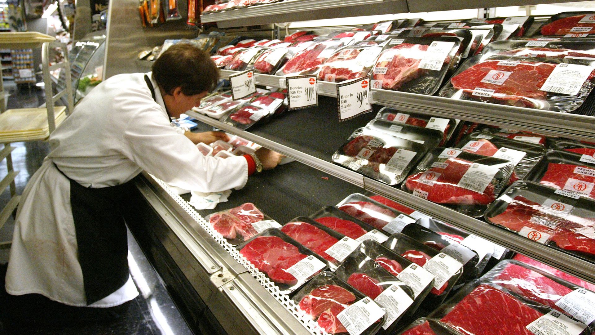 A butcher arranges meat products.