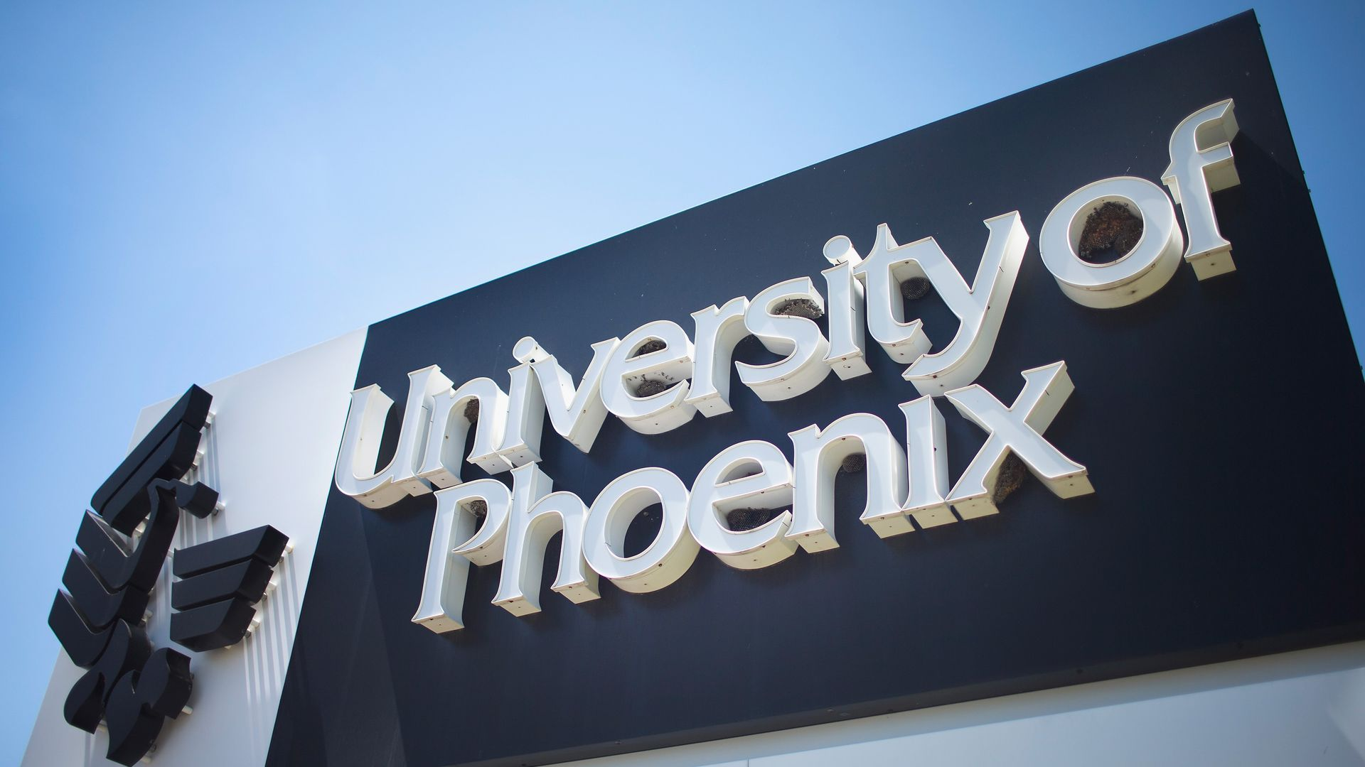 """In this image, a campus sign reads """"University of Phoenix"""""""