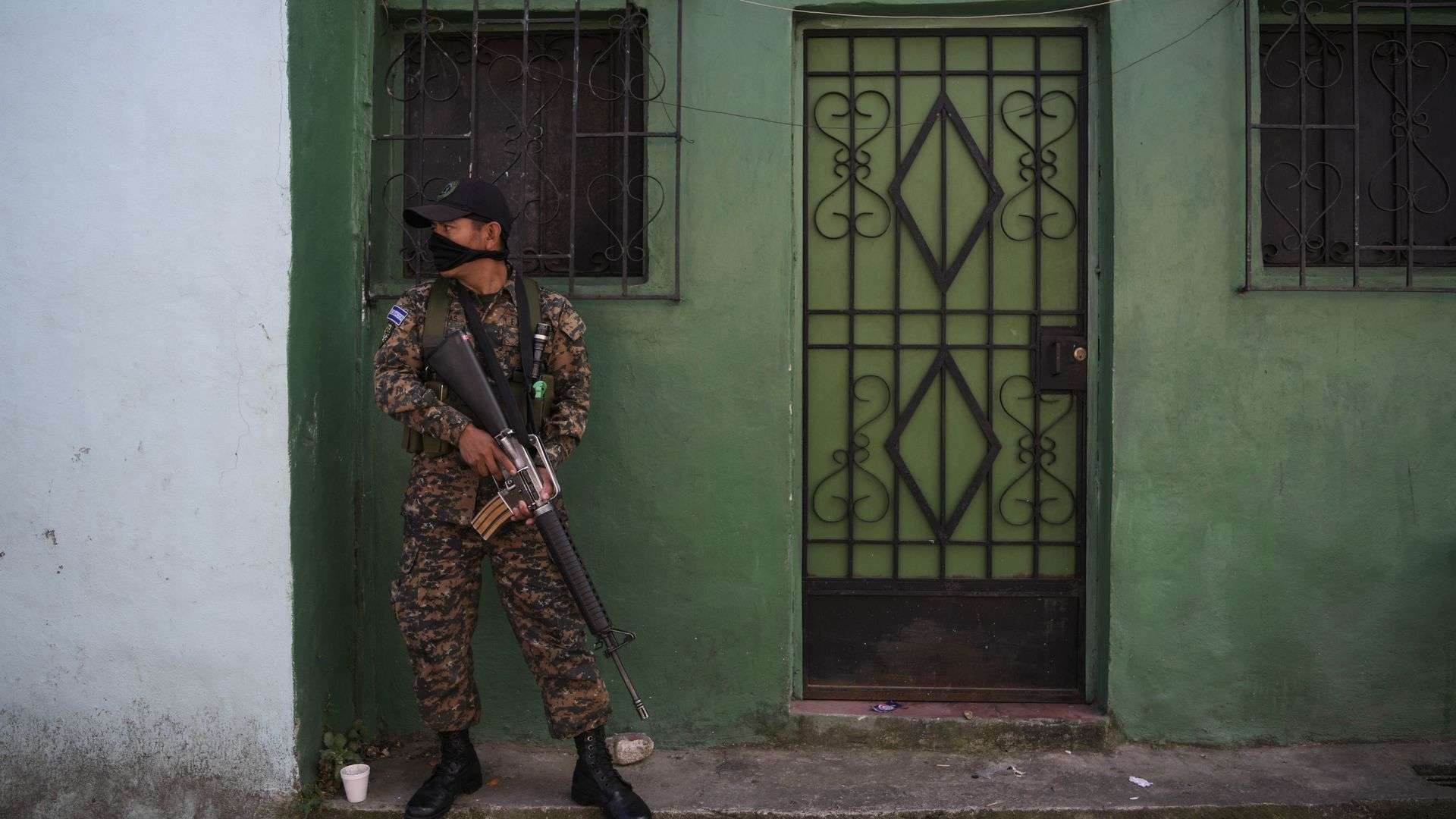 In this image, a Salvadoran army soldier patrols in a neighborhood dominated by the MS-13 gang in San Salvador. The soldier stands against a green wall, carrying a rifle.