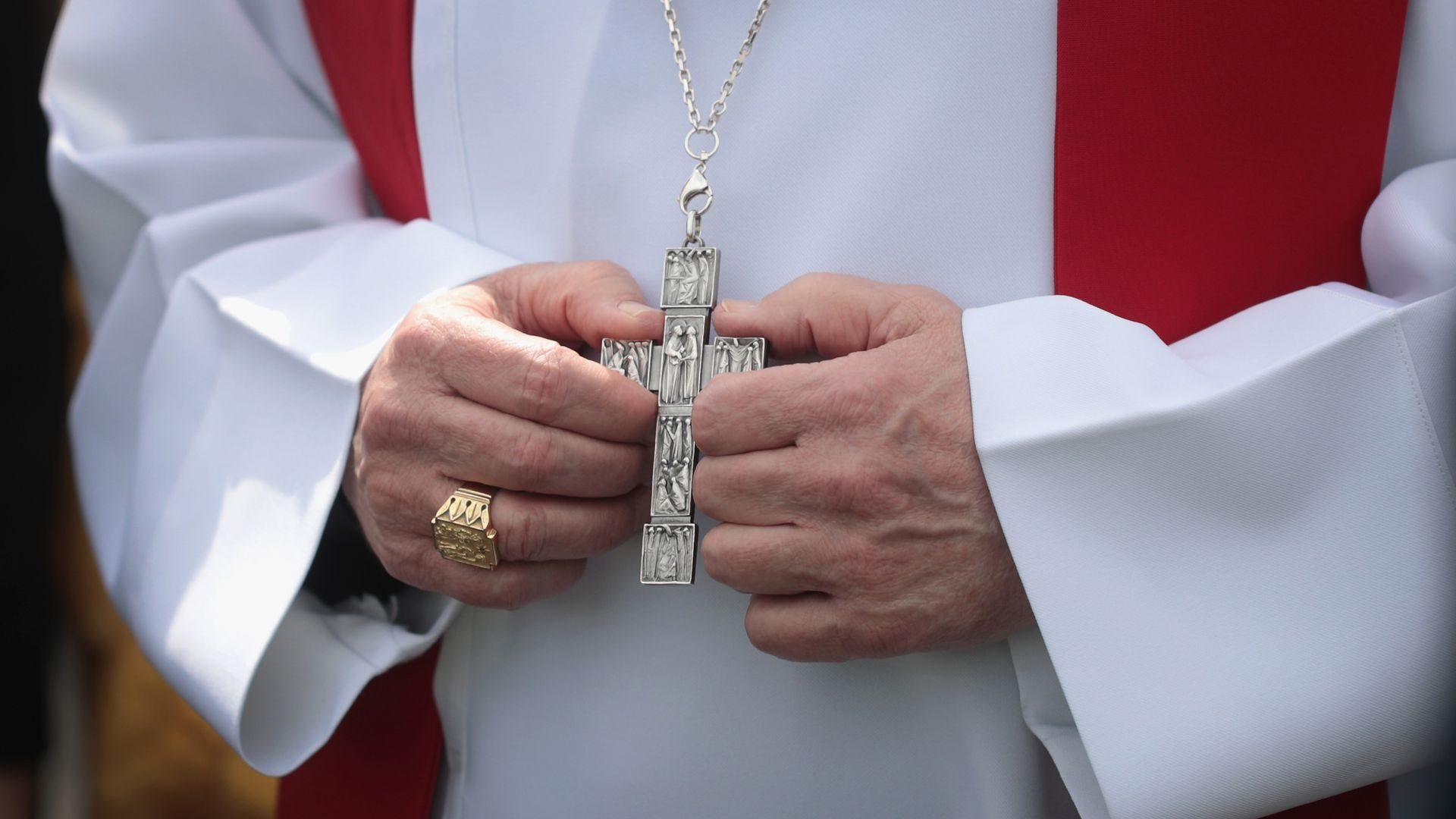 A close-up of a Cardinal's hands holding a cross.