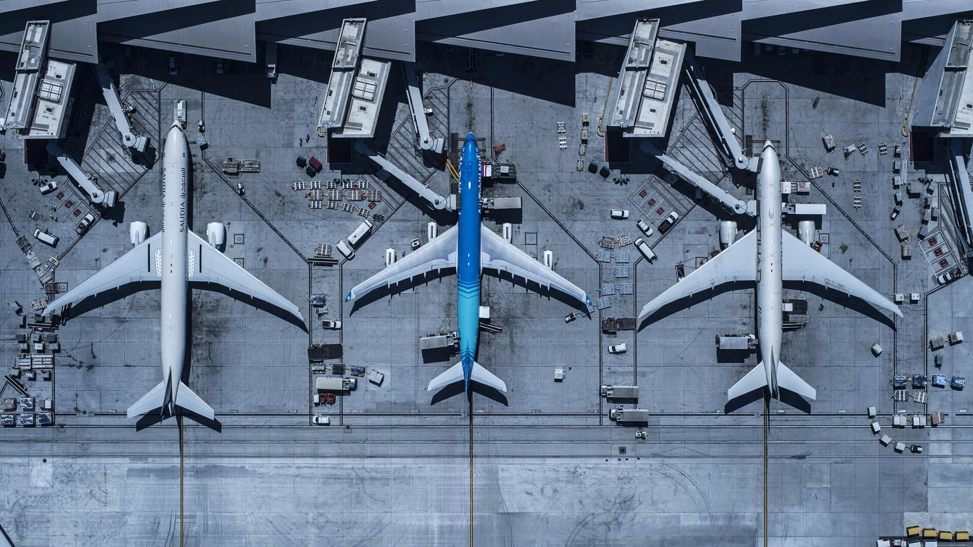Three airplanes docked at airport terminals