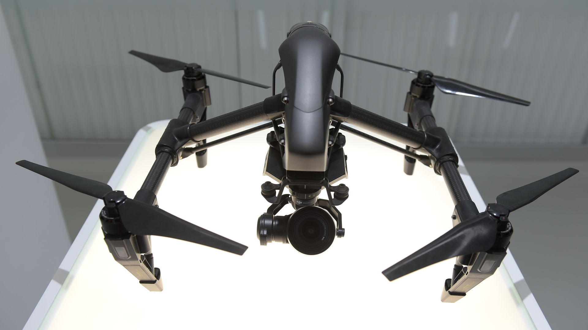black commercial quadcopter drone, sitting on pedestal