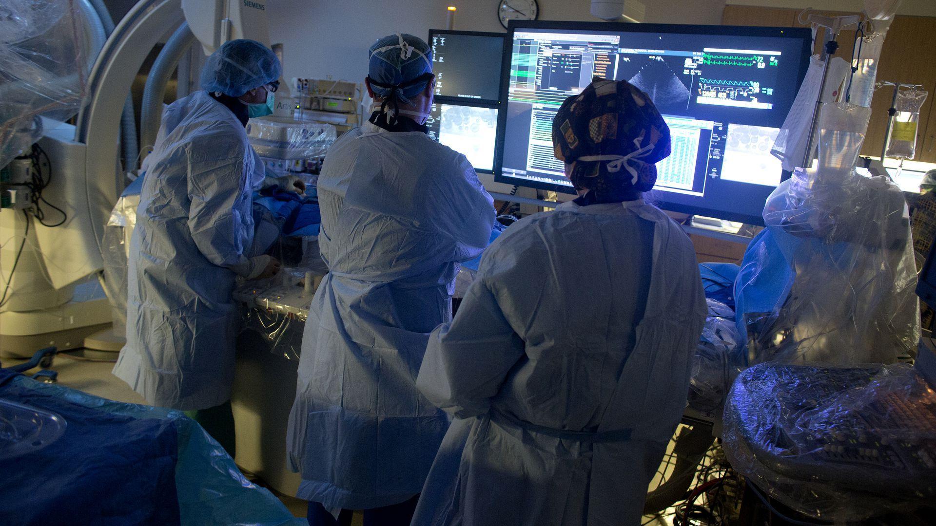 Doctors in sterile garb looking at computers