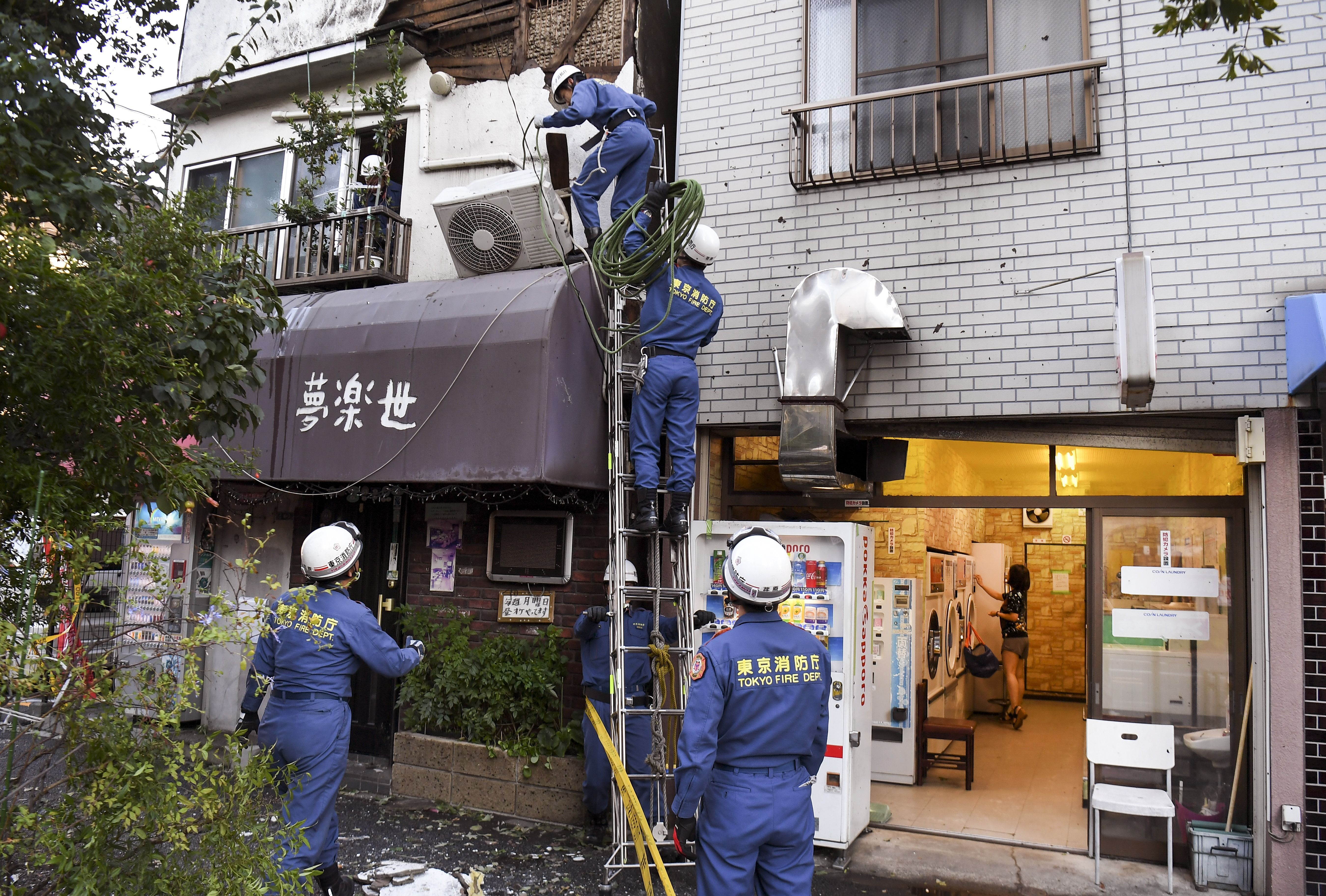 Tokyo Fire Department workers help repair damage in the aftermath of Typhoon Hagibis
