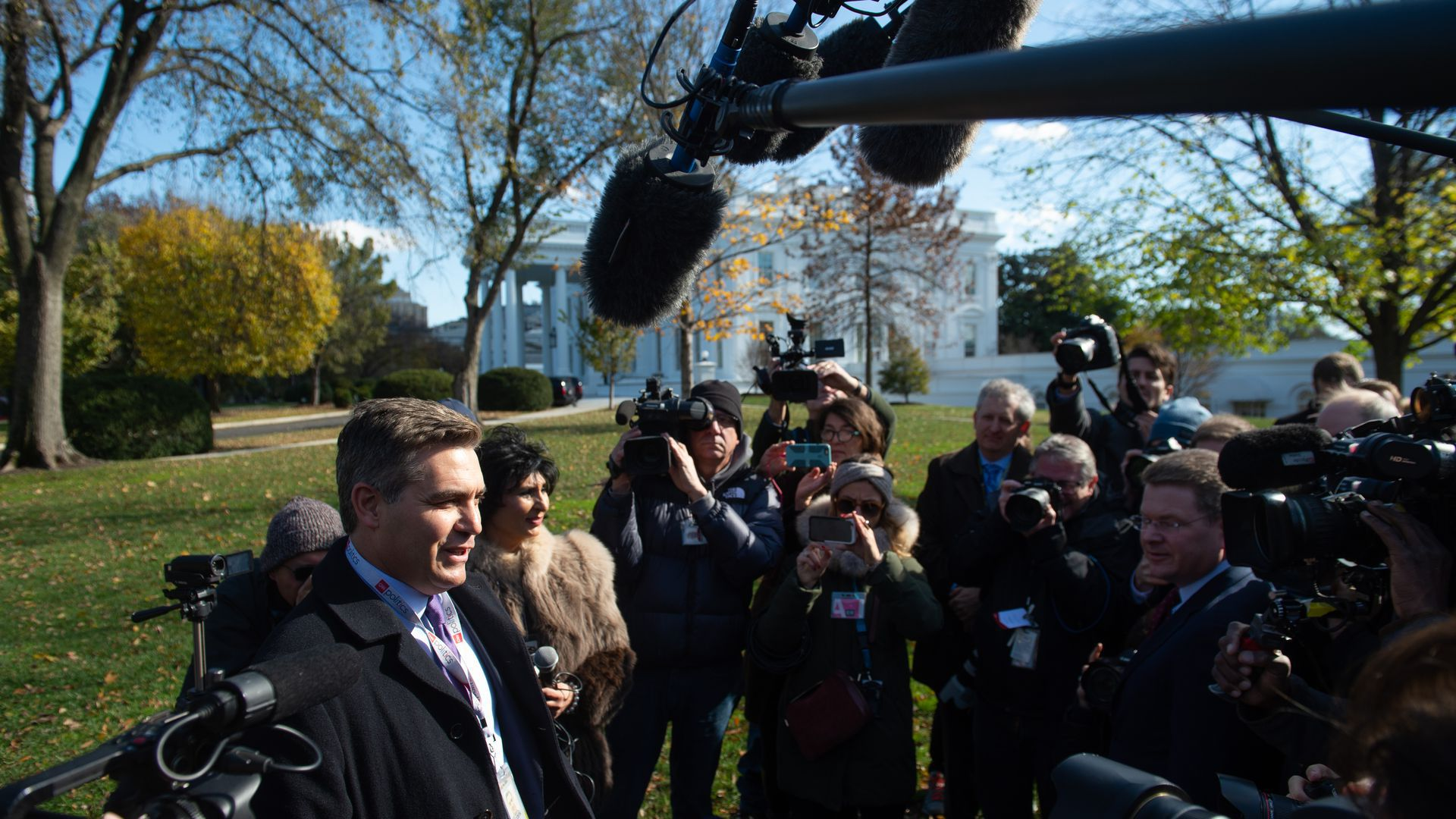 Jim Acosta stands before the press outside of the White House