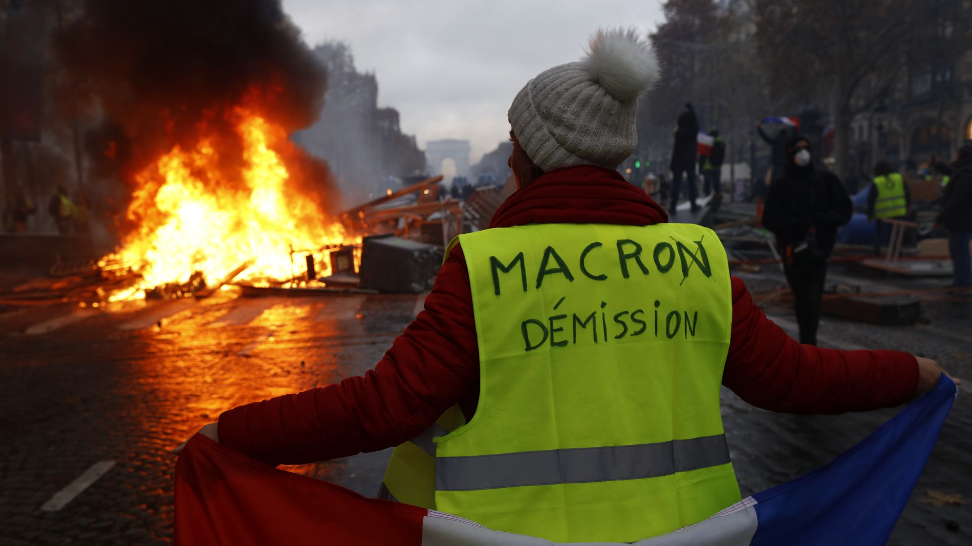 "A yellow vest protester with ""Macron resign"" written on her back."