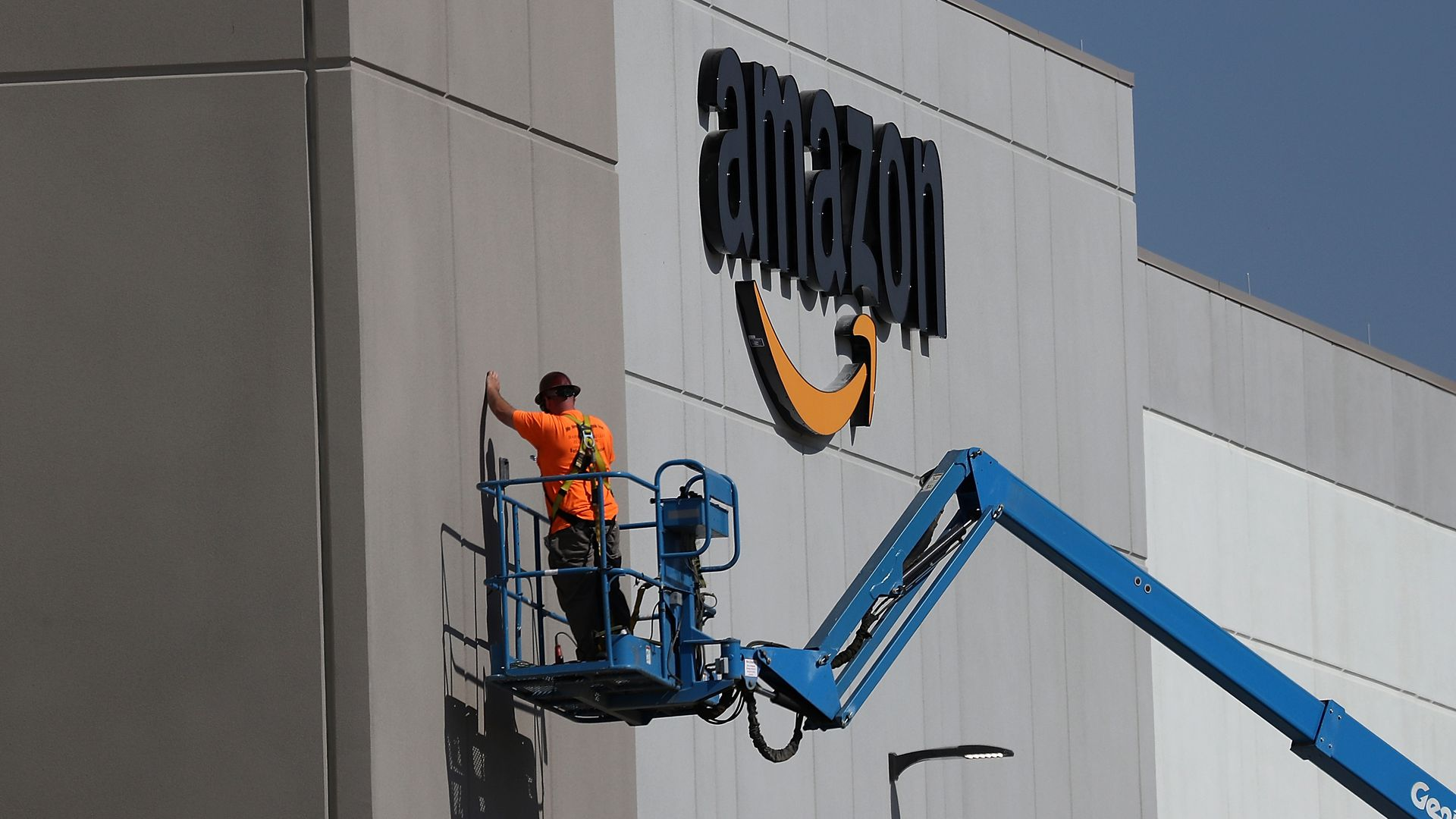 Amazon warehouse with a man on a cherry picker outside.
