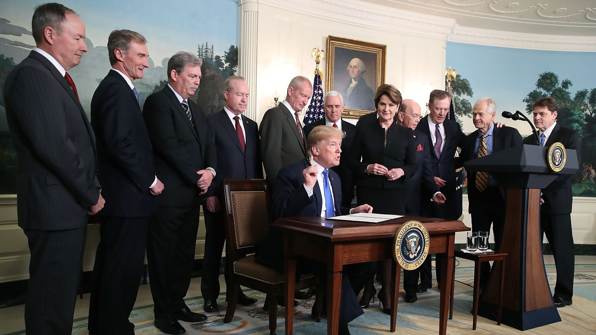 President Trump flanked by members of the business community as he signs a memorandum aimed at what he calls Chinese economic aggression in the Roosevelt Room at the White House on March 22, 2018.
