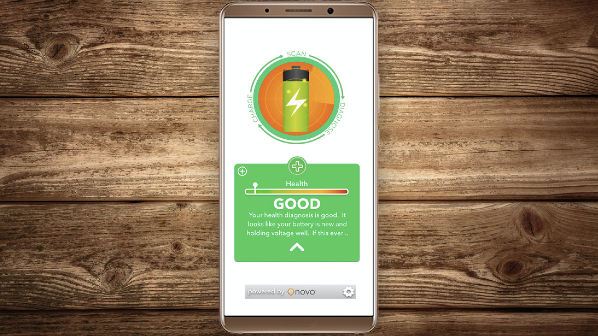 "In this image, a cell phone lays on a wooden table and displays a green battery symbol with a ""Good"" health rating."