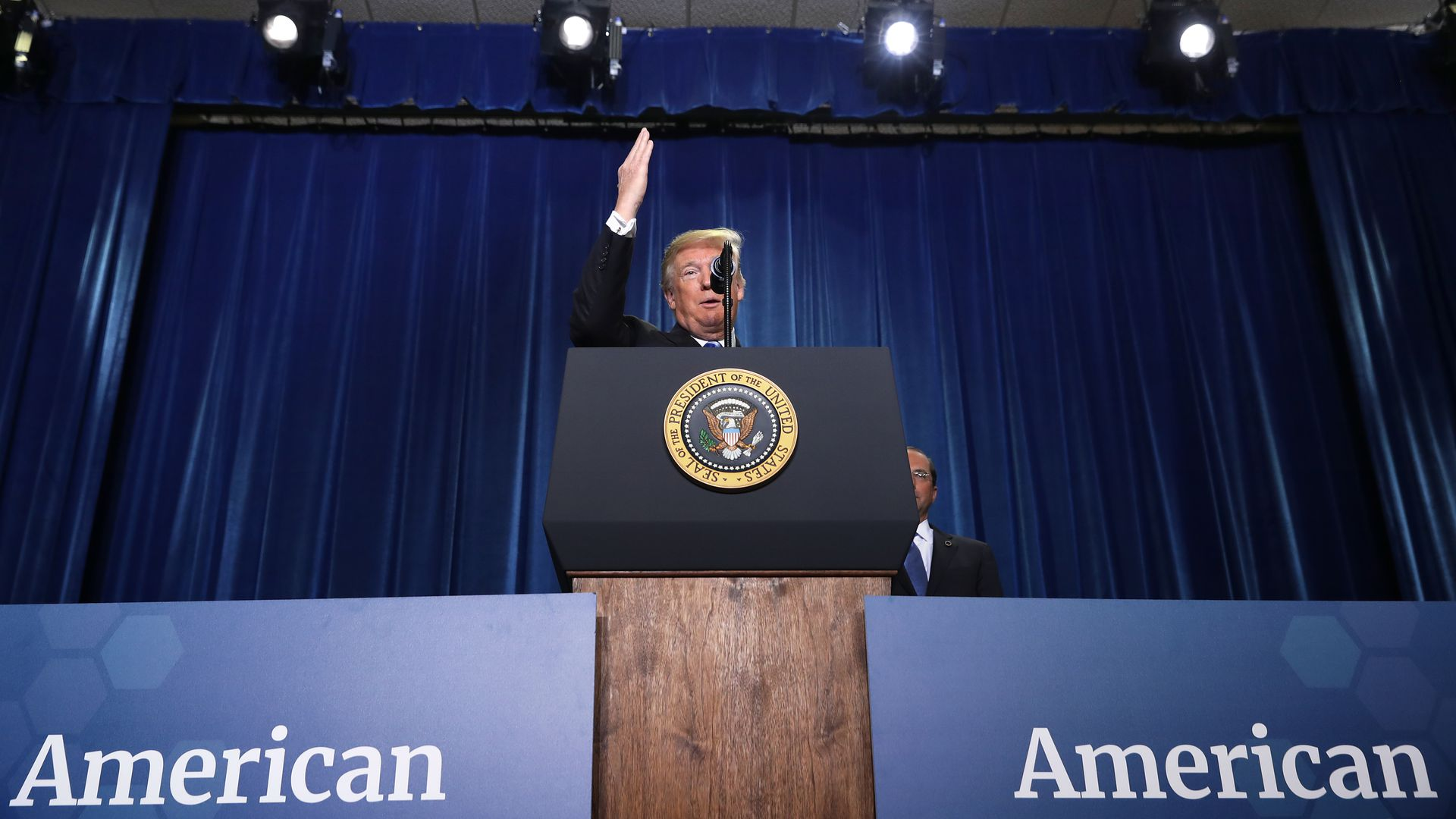 President Donald Trump on stage during a speech at the Department of Health and Human Services