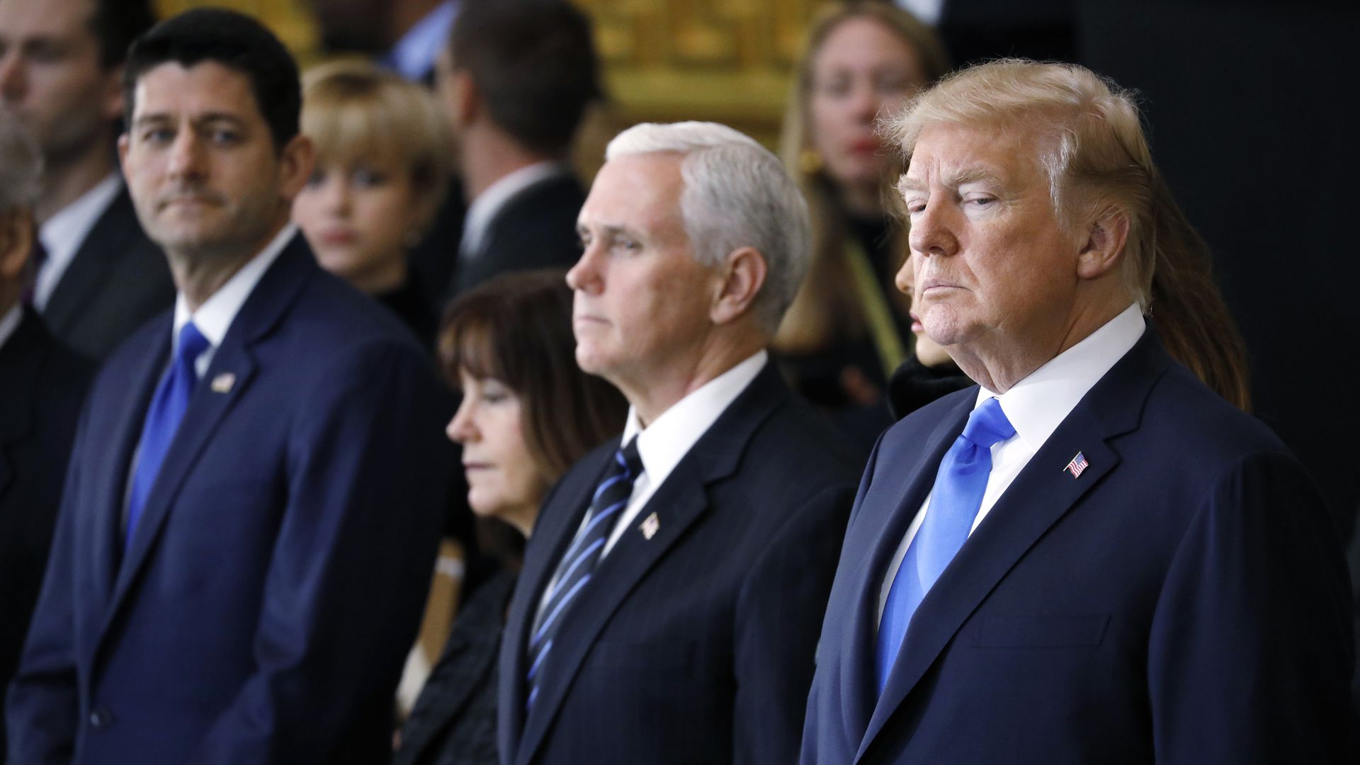 Paul Ryan looking over at Mike Pence and Donald Trump, who is looking down.