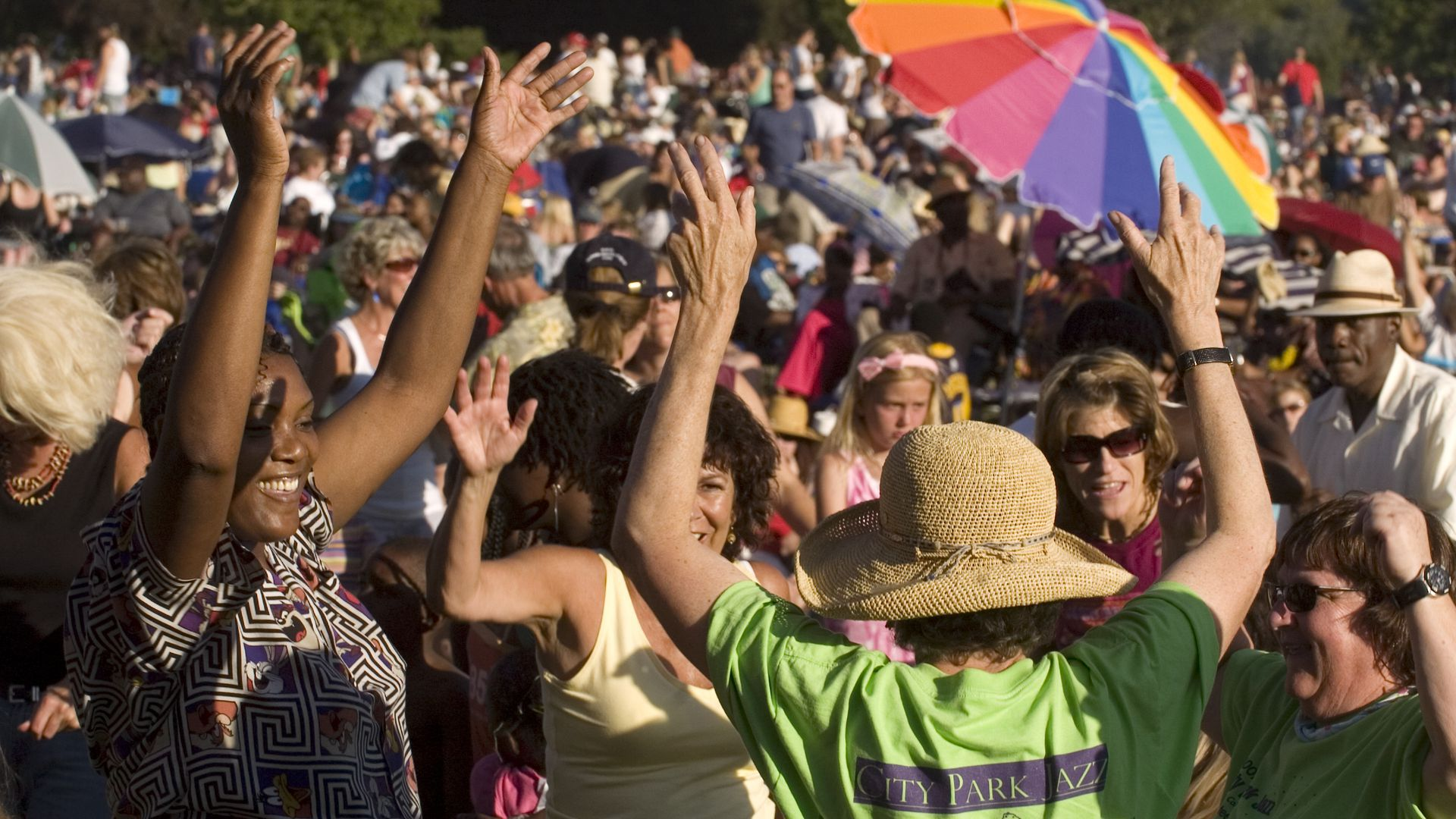 A crowd of people throw their hands in the air at a park