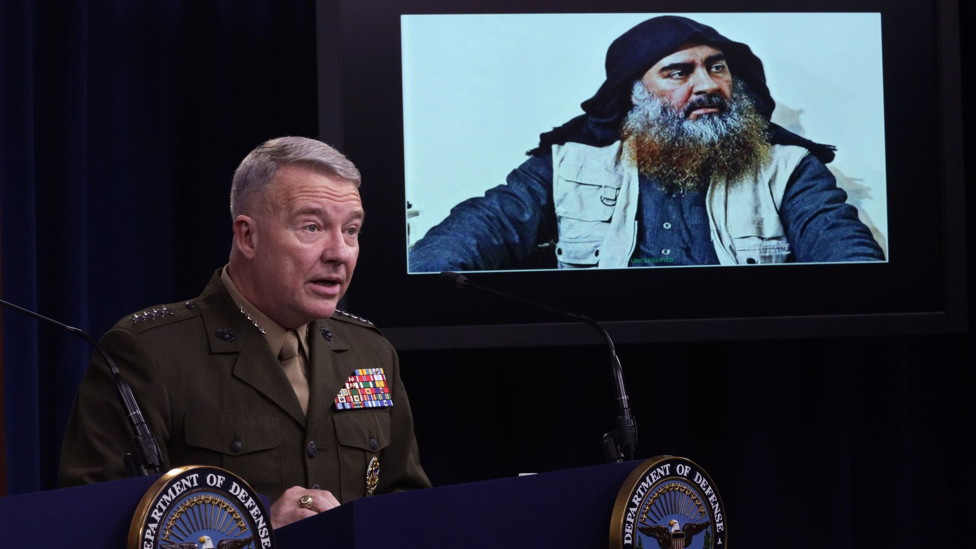 U.S. Marine Corps Gen. Kenneth McKenzie, commander of U.S. Central Command, speaks as a picture of Abu Bakr al-Baghdadi is seen during a press briefing