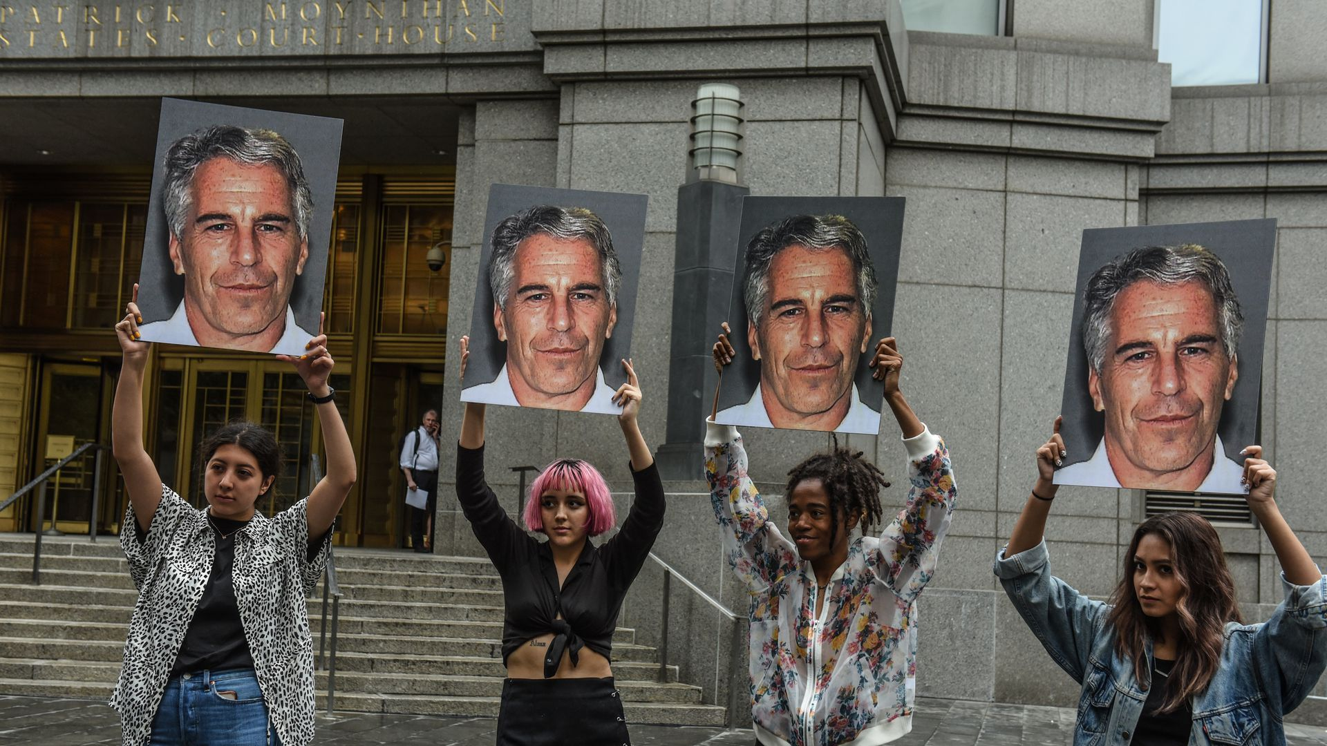 In this image, four people hold up signs of Jeffrey Epstein's face.