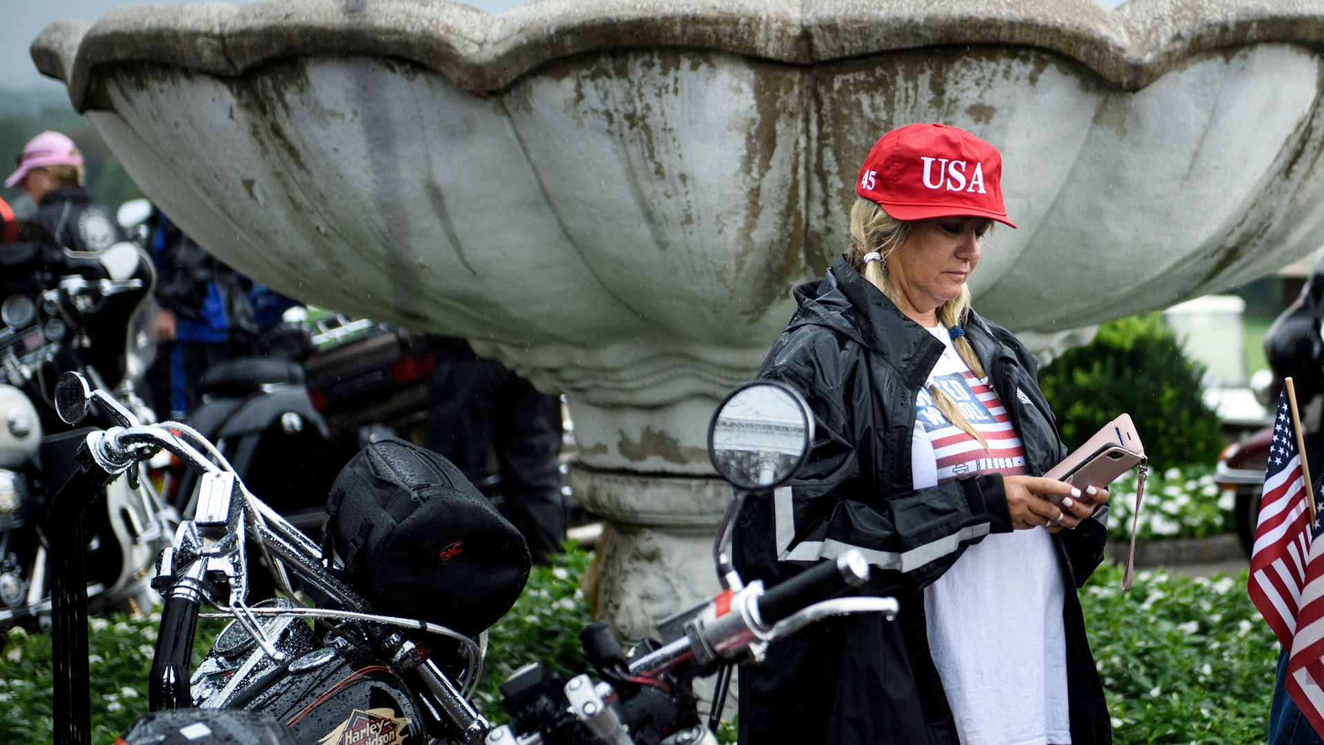 A woman wearing a USA hat looks at her phone.