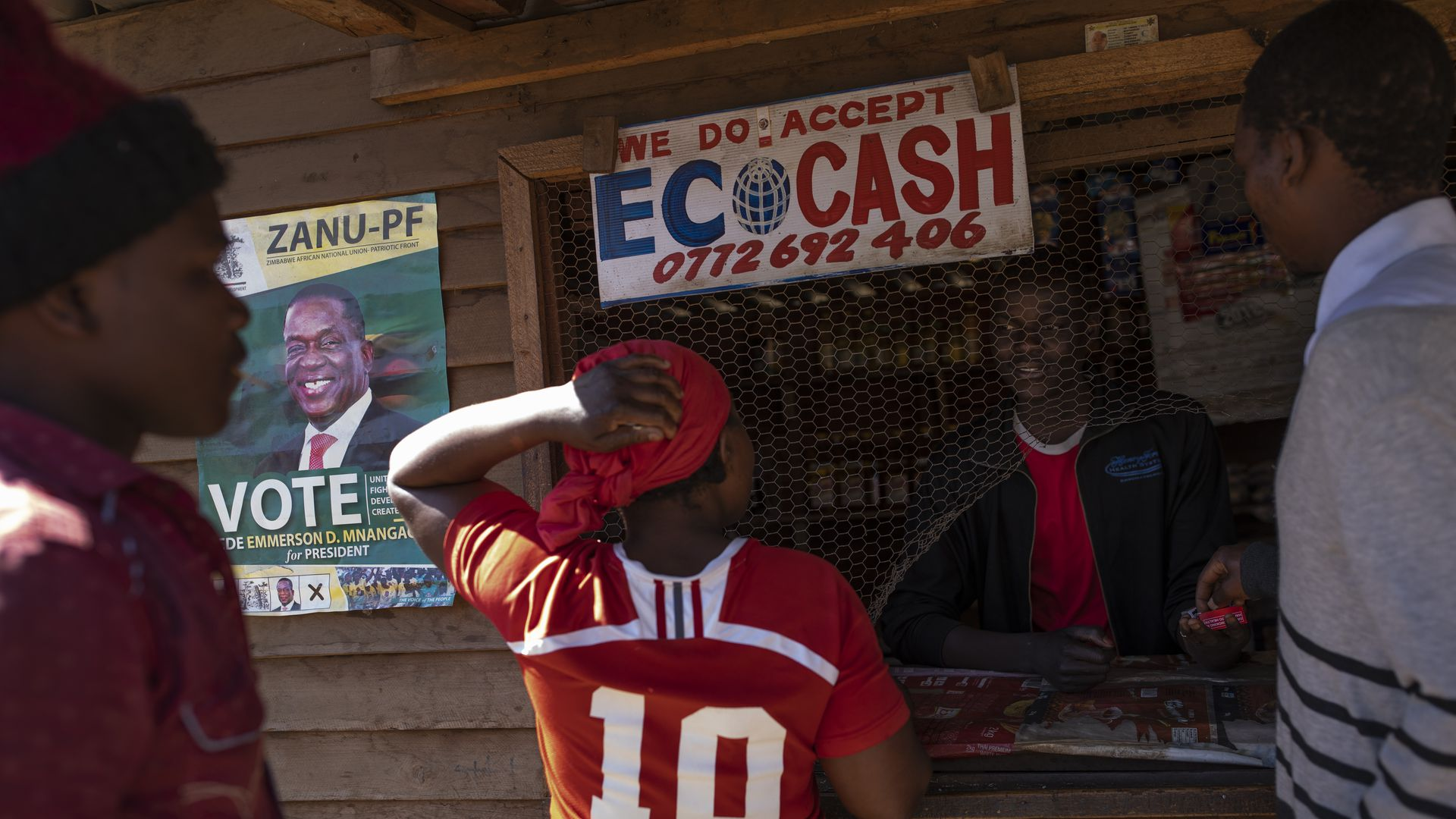 Vendors use a street shack that accepts EcoCash' to buy goods in the Mbare neighborhood on July 27, 2018 in Harare, Zimbabwe.