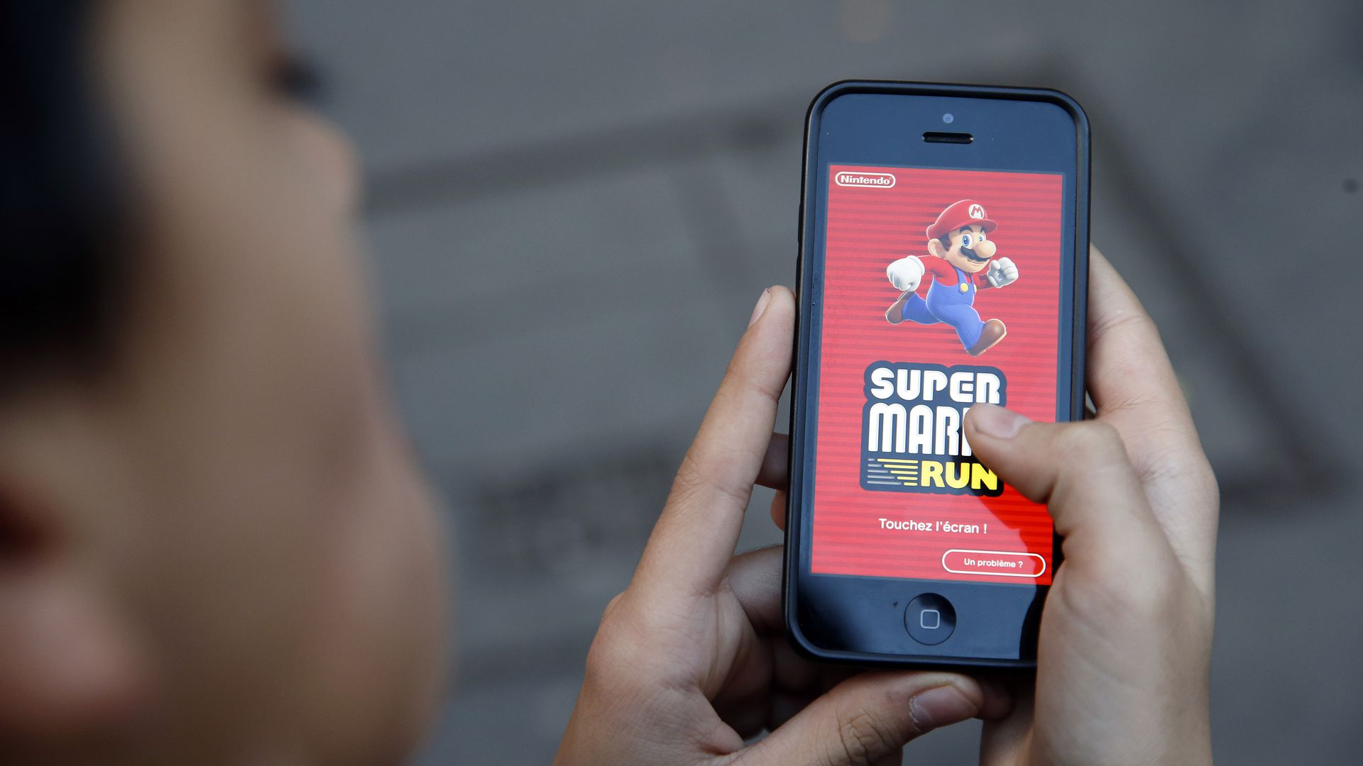 In this image, a woman holds a phone to the camera that displays the Mario Run game logo.