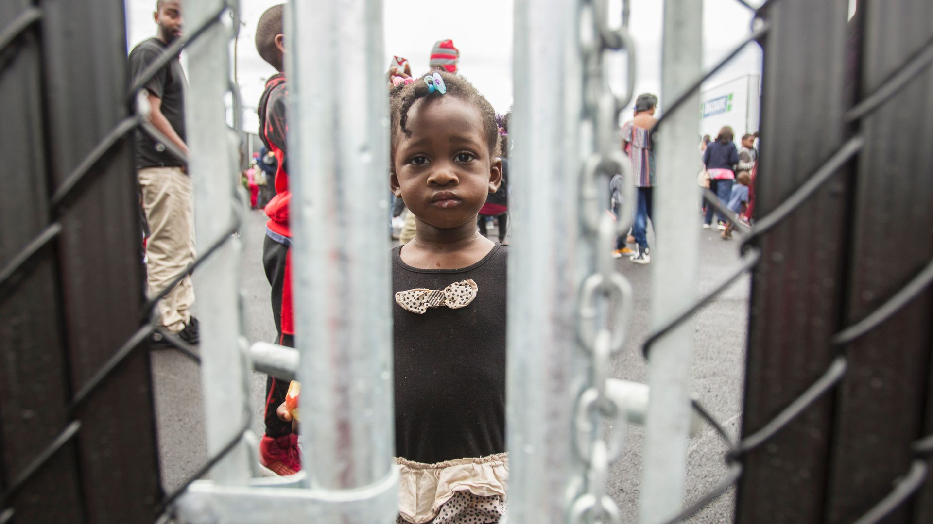 Little black girl with pink bows looks through chain linked fence with a frown.
