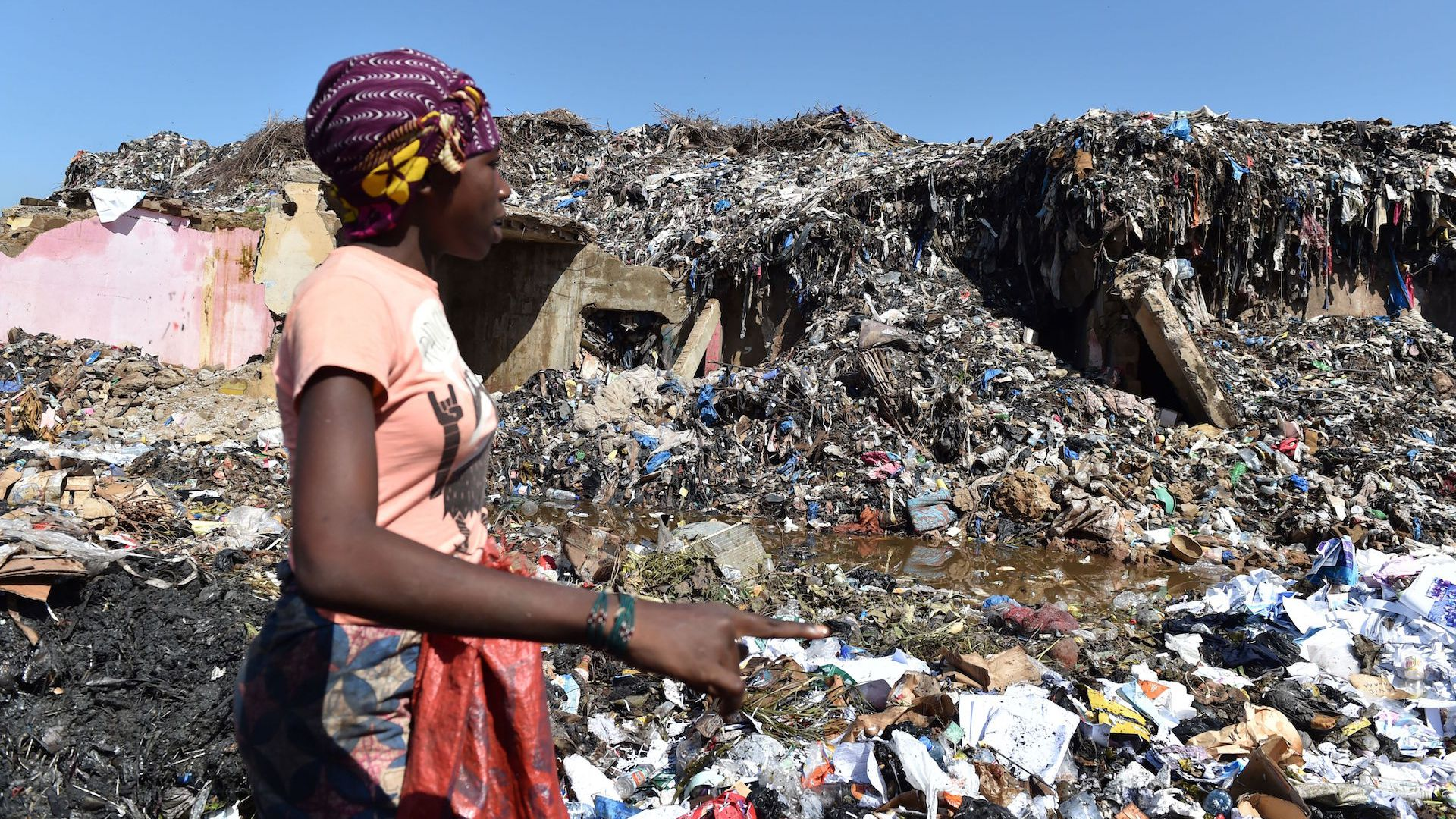 A woman looks for valuables in a rubbish dump containing plastics pollution in Bamako on August 16, 2018.