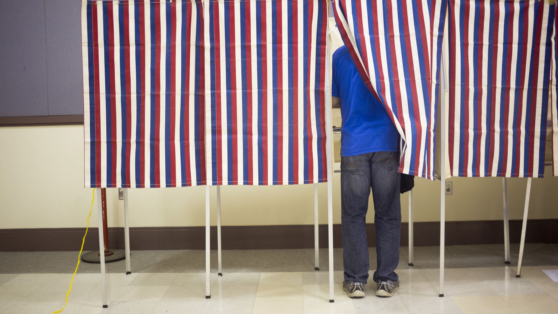Red, white, and blue striped panels cover a voter voting in a polling booth.