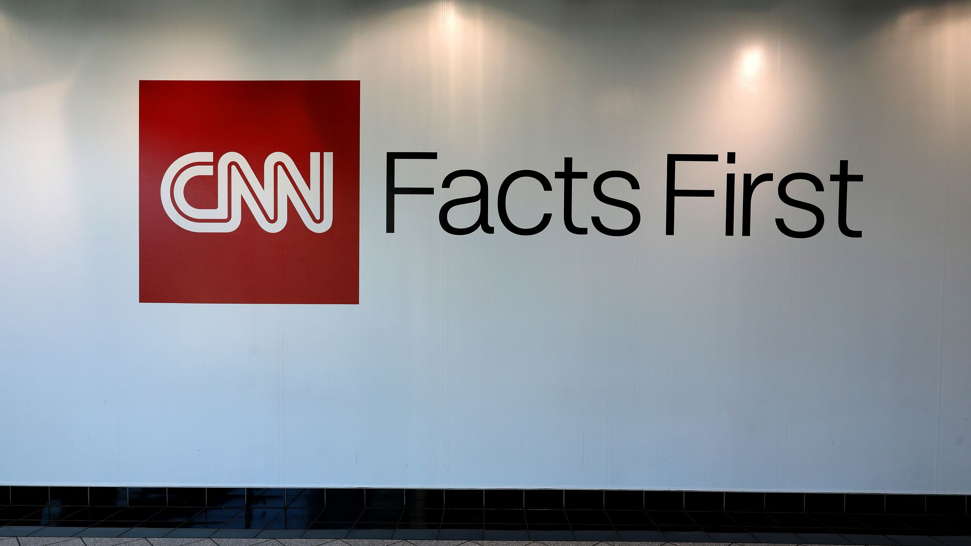 """CNN, Facts First"" is written on a white wall."