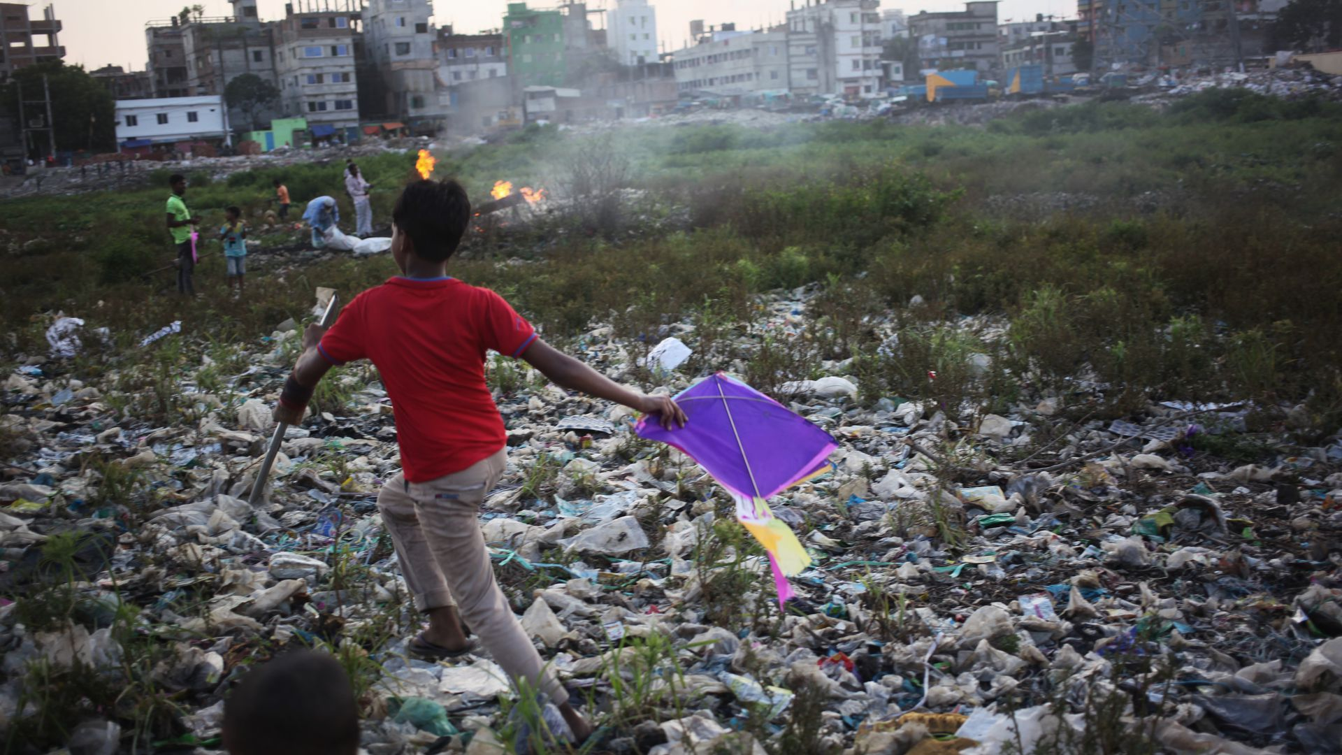 In this image, a boy in a bright shirt carries a kite while running over a field of garbage.