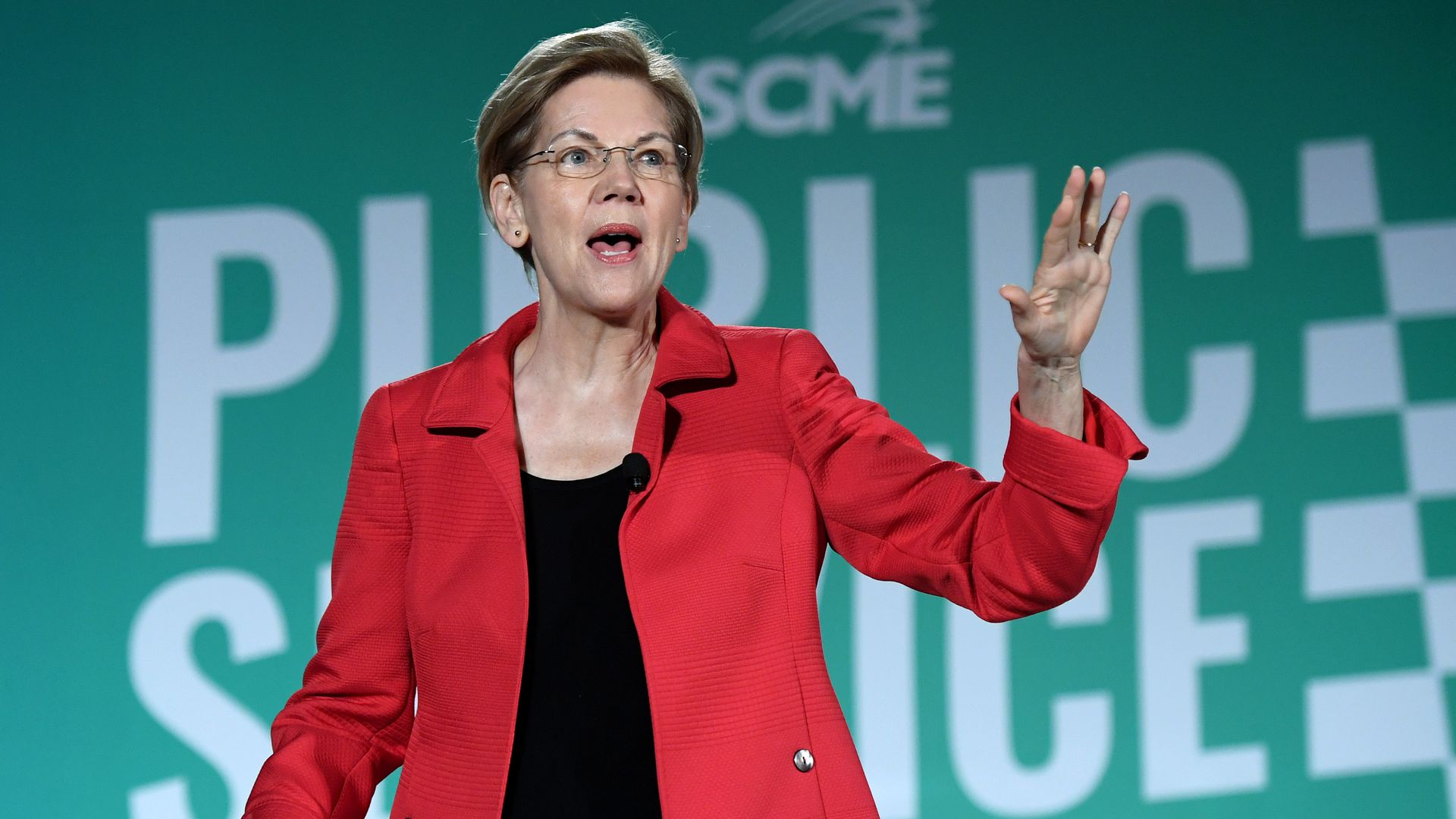 In this image, Warren wears a blazer and speaks on a stage.