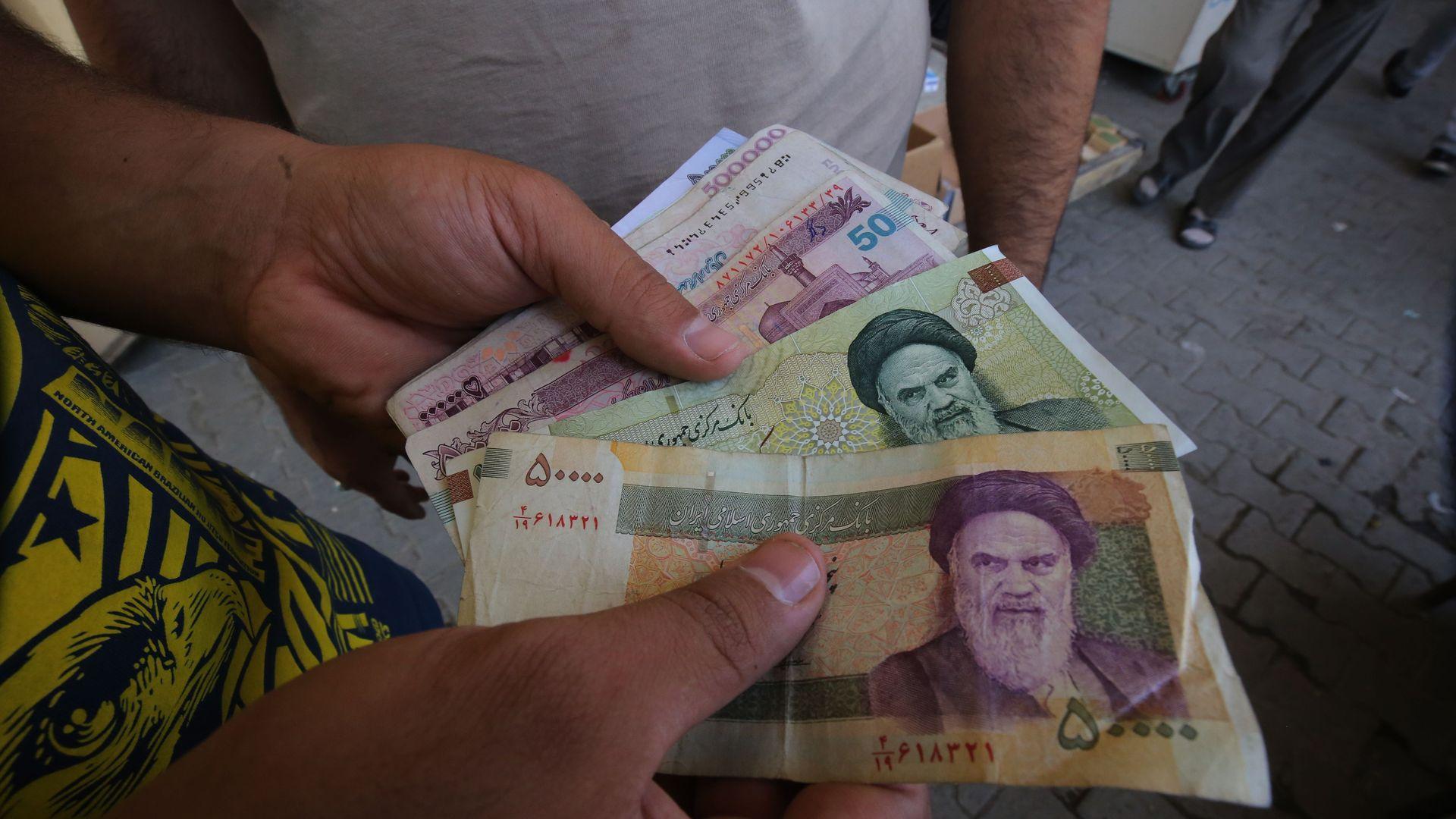 Iraqi man holding Iranian rials