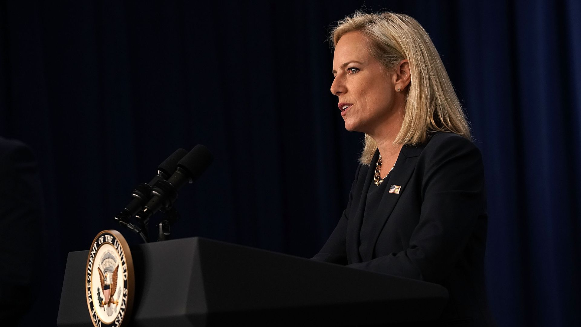Kirstjen Nielsen speaking at a podium.