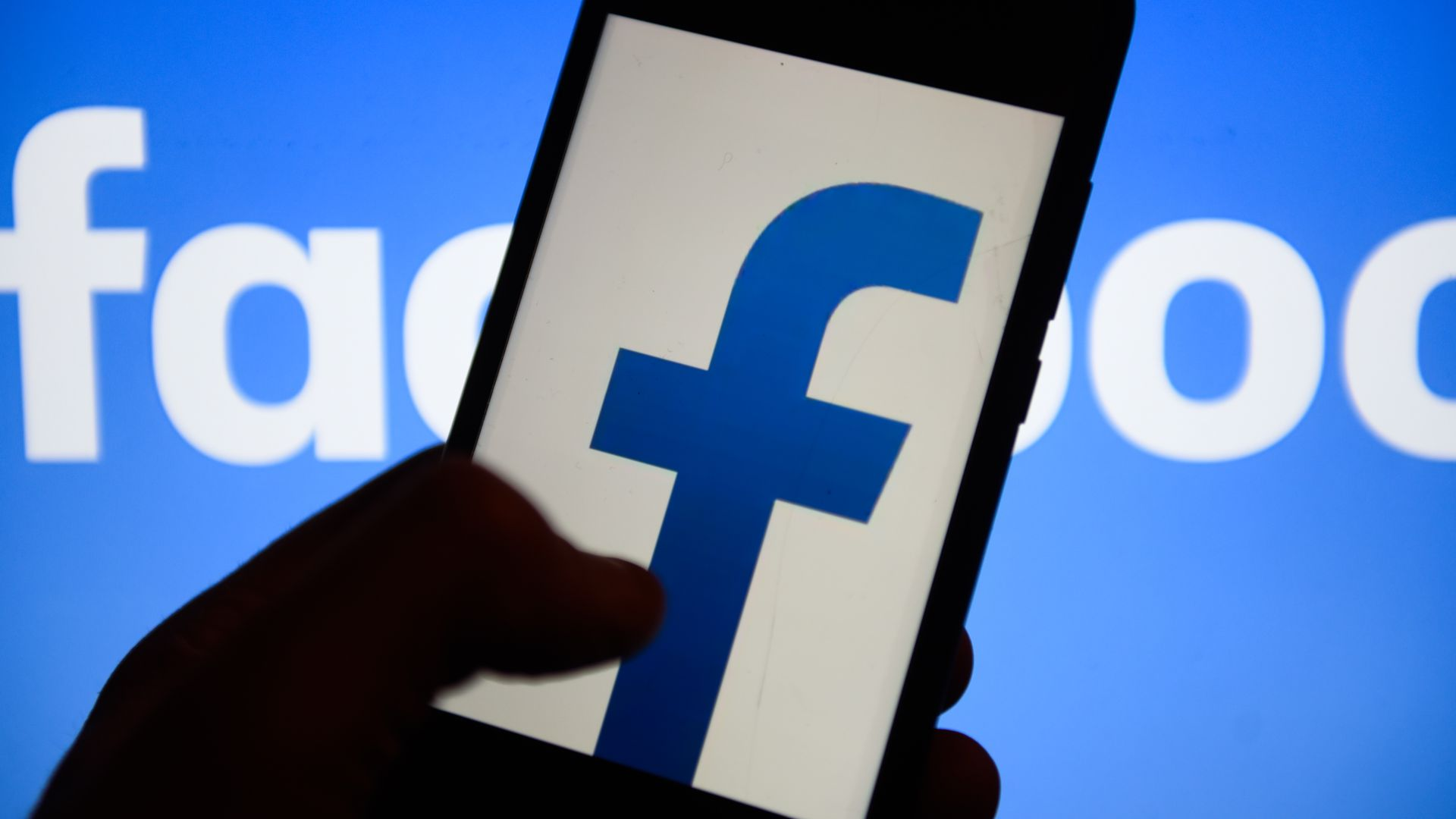 Facebook logo on smartphone screen with shadowy fingers