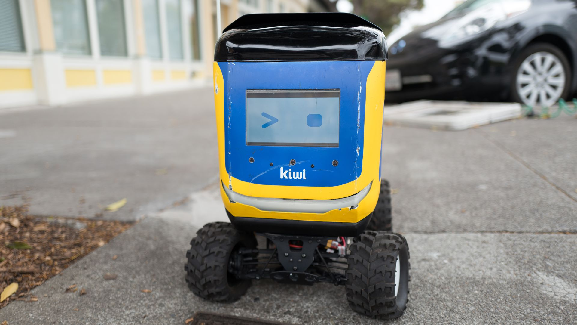 Front view with digital face of Kiwi self driving autonomous package delivery robot parked in Berkeley, California