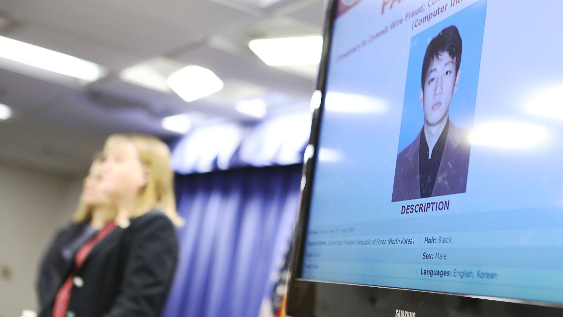 Justice Department officials in the background of a monitor displaying a North Korean man.