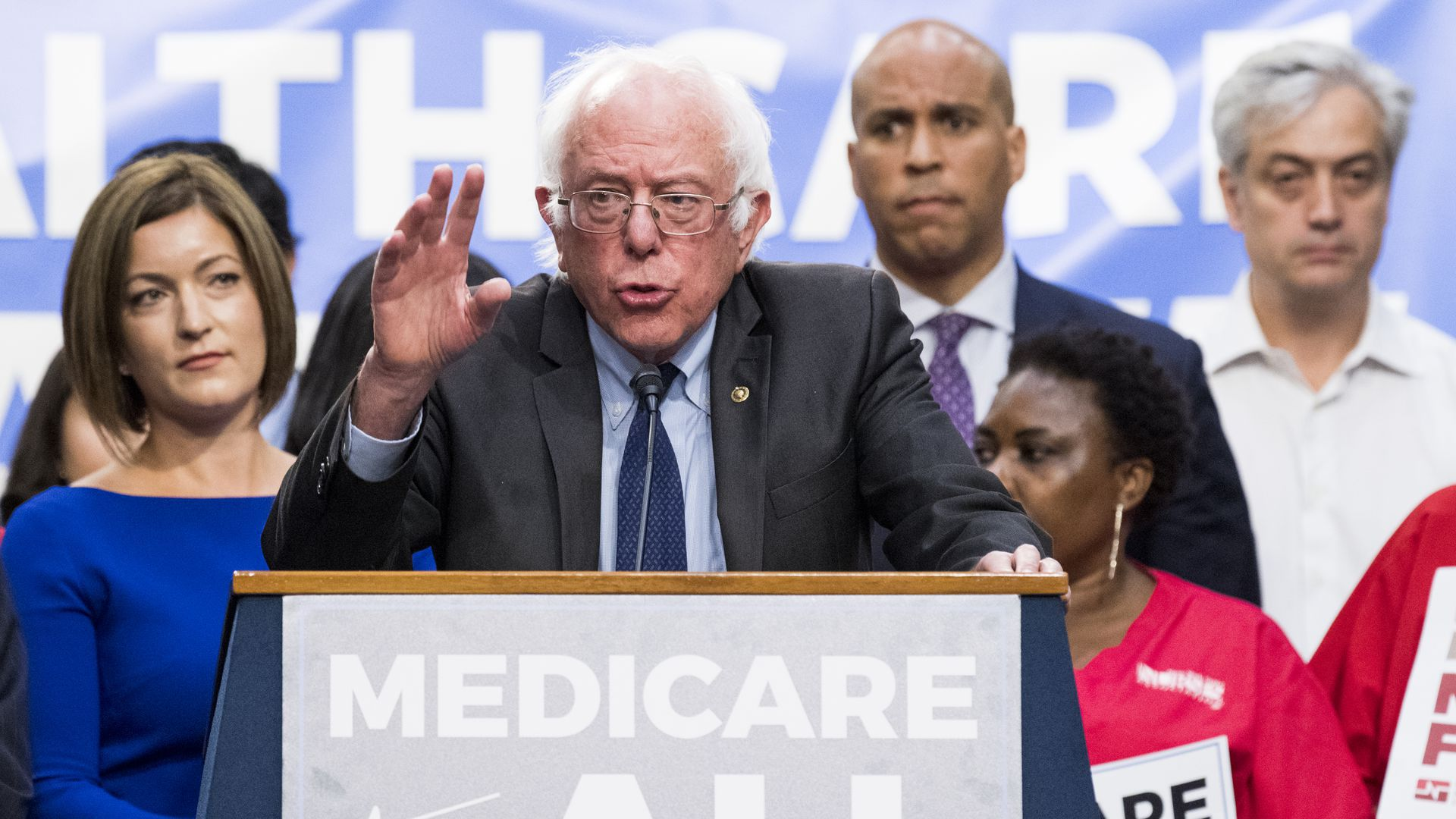 Bernie Sanders behind a Medicare for All lecturn