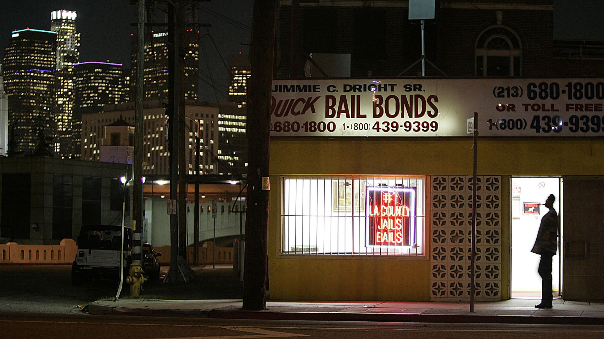 The lights of downtown Los Angeles shine behind a Quick Bail Bonds building across from the Men's Central Jail.